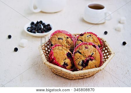 Muffins with black currants in a wicker basket on a light concrete background. American cuisine. Copyspace. Selective focus stock photo