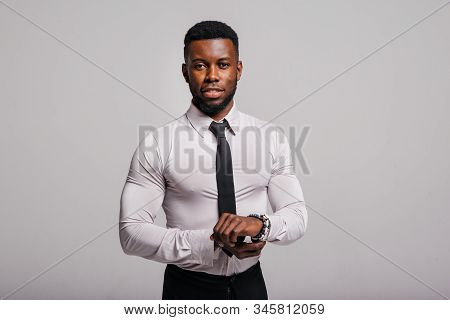 Happy confident young african american business male smiling with confidence, executive stylish company leader. Portrait of an businessman wearing suit and tie isolated on white background stock photo