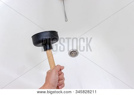 Woman hand holding a plunger to clean bathtub drain, sewer clogged, blocked with fallen out hair stock photo