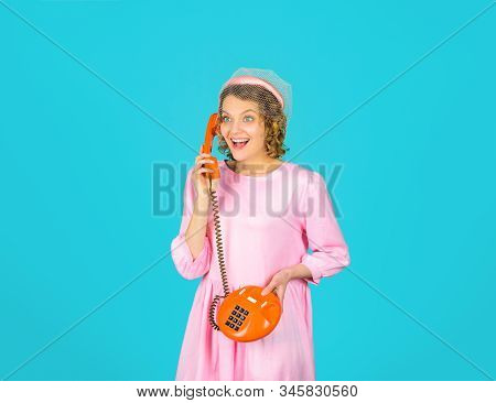 Communication. Woman talking on retro phone. Lovely woman in pink dress with telephone handset. Happy woman holds handset. Woman talking at retro handset. Girl talking on landline phone. stock photo