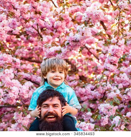 Father and son. Father With Son Having Fun In Park. Dad and son playing together outdoors stock photo