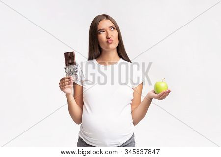 Puzzled Pregnant Woman Choosing Between Chocolate And Green Apple Standing In Studio On White Background. Pregnancy And Nutrition. stock photo