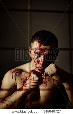 Psycho mad man. Psychic disease. Murderer brutal aggressive guy. Fight and attack. Aggressive person. Strong aggressive monster behind grid. Bodybuilder nude torso soiled blood. Prison for monster. stock photo