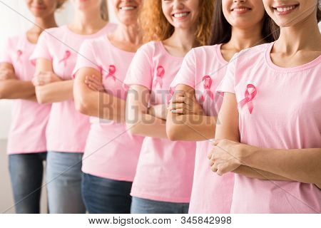 Breast Cancer Survivors. Group Of Diverse Women In Pink Awareness T-Shirts Standing In Line On White Background. Cropped, Shallow Depth stock photo