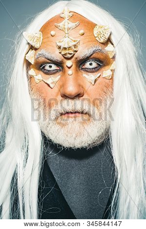 Ancient alchemy. Monster with white blue eyes. Wizard demon man with dragon skin and horns. Devil horror concept. Elderly man holding two red horns. Dracula - Halloween concept stock photo