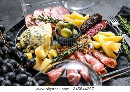 Typical italian antipasto with prosciutto, ham, cheese and olives. Black background. Top view stock photo