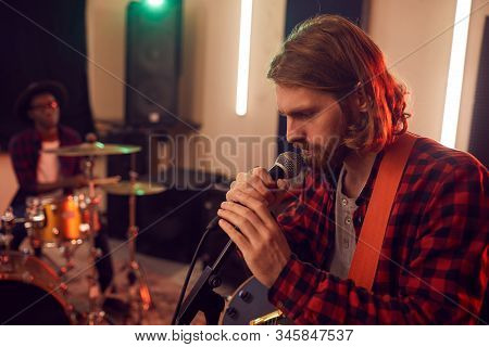 Side view portrait of handsome bearded man singing to microphone during rehearsal or concert with music band in dimly lit studio, copy space stock photo