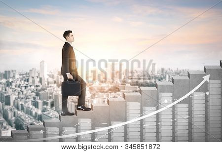 Business man climbing up stair steps to career success with business district and horizon skyline as background. Concept of business goal success, growth of career path and starting up a new business. stock photo