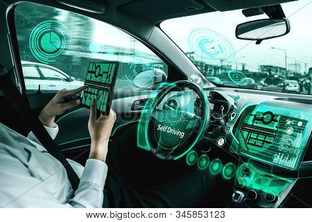Self-driving autonomous car with relaxed young man sitting at driver seat is driving on busy highway road in the city. Concept of machine learning, artificial intelligence and augmented reality. stock photo