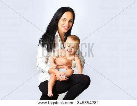 Mother hugging and carrying her baby. Family concept. Mothers Day. Young mother holding her newborn child. Isolated on white background. A young and slim mother stock photo