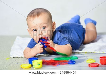 Baby child draws with colored paints hands. Lifestyle childhood concept. Happy child draws. Painted in skin hands. Portrait of sweet baby. Water colors. Child portrait. Copy space stock photo