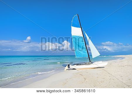 Catamaran landed on the beautiful beach of Varadero in Cuba. Tourist attractions on the Caribbean coast. Sailboat on the background of clear turquoise water in the sea and sky. stock photo