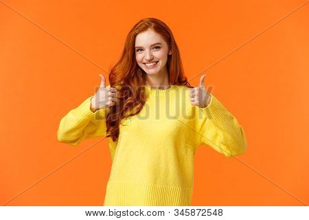 Confident and caring good-looking redhead sister rooting for sibling, saying yes, approving choice, recommend product, show thumbs-up and nod acceptance, smiling positive reply, orange wall stock photo