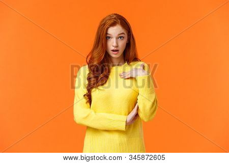 Who me. Frustrated and shocked, confused redhead woman accused, pointing herself and gasping stare astounded, feeling hurt person blame her, receive accusations, orange background stock photo