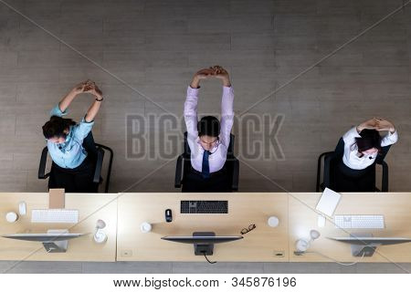 Late Night Environment, Top view of young adult friendly operator team with headsets stretch after all day hard working. Using for 24 Hr. Call center Concept. stock photo