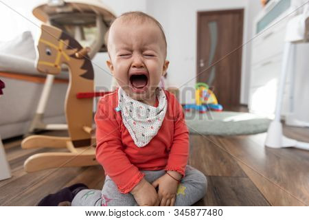 Little girl sitting on the floor at home and crying. One year old baby crying stock photo
