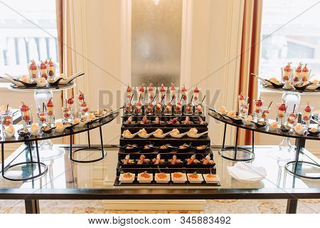 Delicious Snacks Assortment on Glass Table Photo. Seafood and Sweet Ripe Fruits. Shrimps, Fish Meat and Caviar Seasoned Green Leaves. Catering Service. Room Interior and Windows on Background stock photo