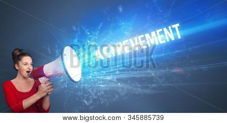 Young person shouting in loudspeaker with ACHIEVEMENT inscription, business concept stock photo