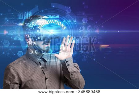 Businessman looking through Virtual Reality glasses with INNOVATIONS inscription, innovative technology concept stock photo