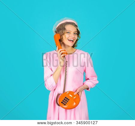Girl talking on landline phone. Happy woman holds handset. Young woman talking on retro phone. Smiling woman in pink dress with telephone handset. Pretty woman talking at retro handset. Communication. stock photo
