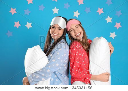 Beautiful women with pillows on light blue background. Bedtime stock photo