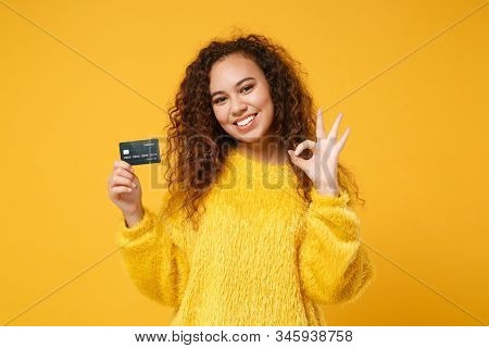 Pretty young african american girl in fur sweater posing isolated on yellow orange background studio portrait. People lifestyle concept. Mock up copy space. Hold credit bank card, showing OK gesture. stock photo