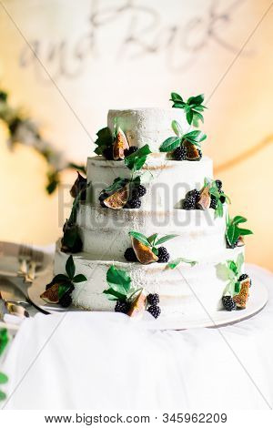 Naked wedding cake. White four-tiered wedding rustic cake with berries and figs and greenery, on the background of white arch stock photo