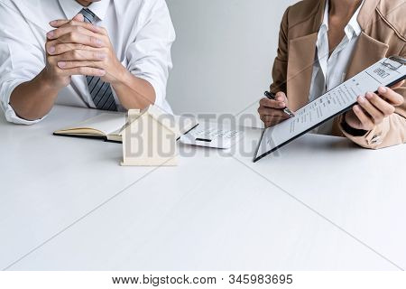 Real estate broker agent presenting and consult to customer to decision making sign insurance form agreement, home model, concerning mortgage loan offer for and house insurance. stock photo