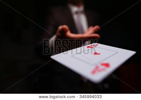 Close-up of man in presentable suit throwing playing card ace of hearts to opponent on dark background. Winning in business and risky avid player concept stock photo