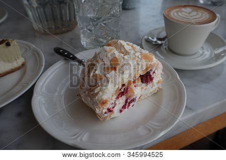 dessert with whipped cream. Pavlova dessert on a plate.  fork stuck in dessert. Piece of homemade dessert Pavlova with cherry and chocolate on a plate stock photo