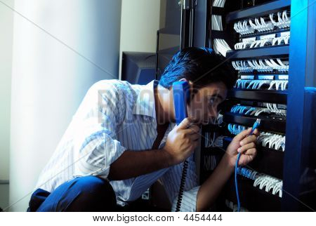 IT system administrator talking on phone while holding a internet cable taken in server room stock photo