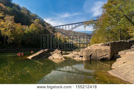Kayakers float towards the rapids under the high arched New River Gorge bridge in West Virginia stock photo