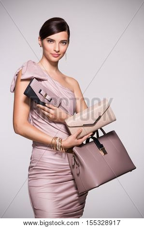 Beautiful glamour woman with jewelry and bag in elegant dress. Fashion girl deciding between clutch bag and purse isolated on grey backgound. Elegant woman with choosing her bag from many purses. stock photo