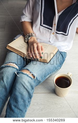 Young Modern Girl In Torn Jeans Reading A Book With A Big Cup Of Coffee. Fashion, Lifestyle, Lifesty