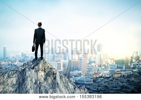 Back view of young man in suit and with briefcase in hand standing on mountain top. City background with copy space. Leadership concept