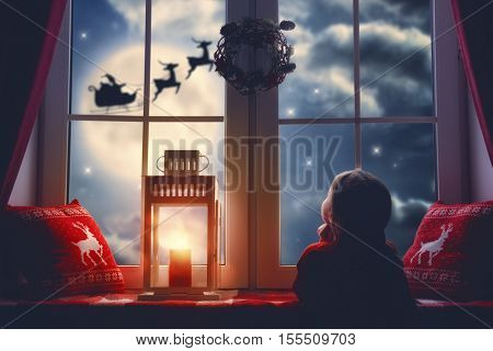Merry Christmas and happy holidays! Cute little child girl sitting by window and looking at Santa Cl