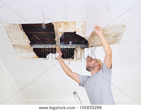 man cleaning mold on ceiling.Ceiling panels damaged huge hole in roof from rainwater leakage.Water damaged ceiling . stock photo