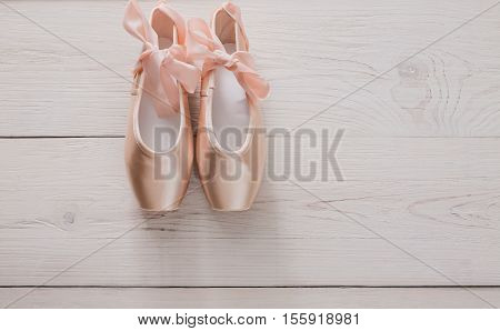 Pastel pink ballet shoes background. New pointe shoes with satin ribbon lay on white rustic shubby chic wood, top view with copy space stock photo