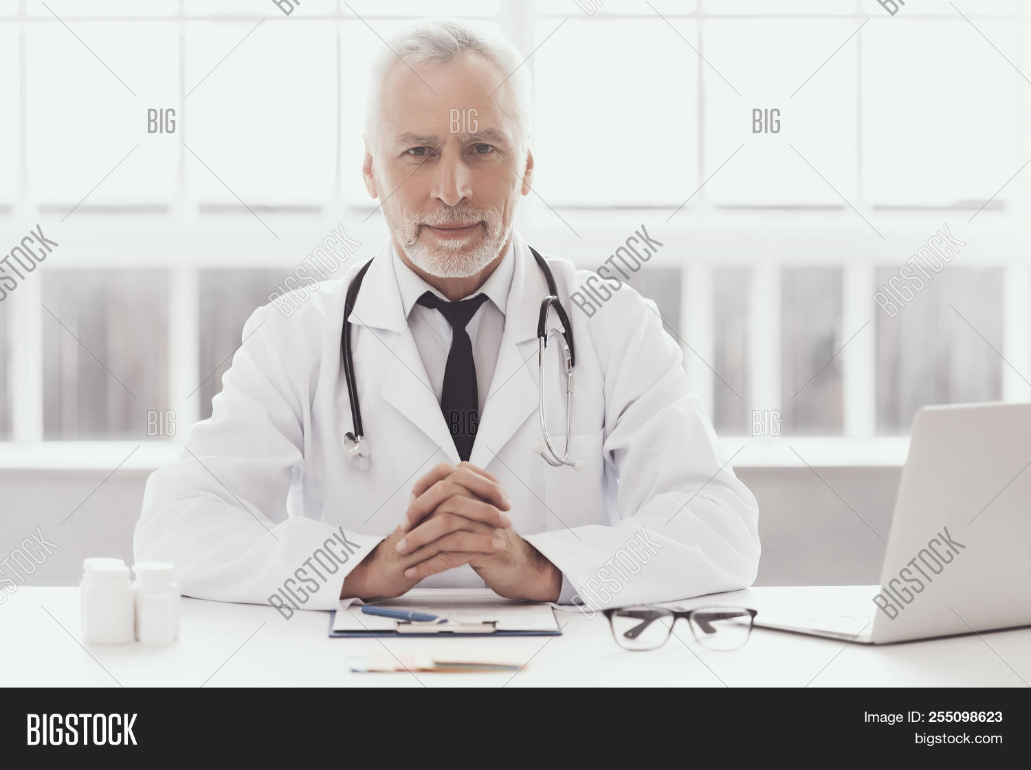 Professional Doctor Sitting In Medical Office. Portrait Of Mature Bearded Smiling Doctor Wearing Whi