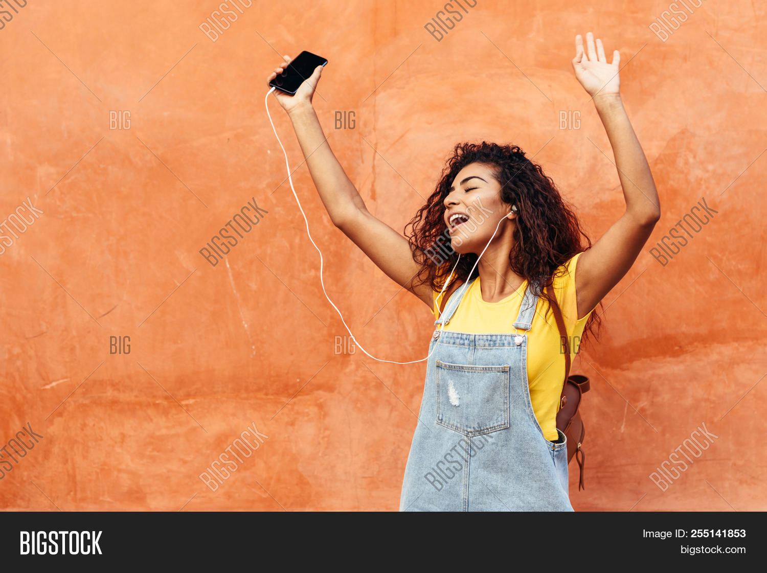 adult,african,arab,attractive,background,beautiful,black,brunette,casual,cell,cheerful,city,clothes,cool,curly,dancing,device,earphones,ethnic,female,girl,hair,hairstyle,happiness,happy,headphones,lady,lifestyle,listening,mobile,modern,music,outdoors,outside,person,phone,portrait,pretty,smart,smartphone,smile,smiling,street,style,technology,urban,woman,young