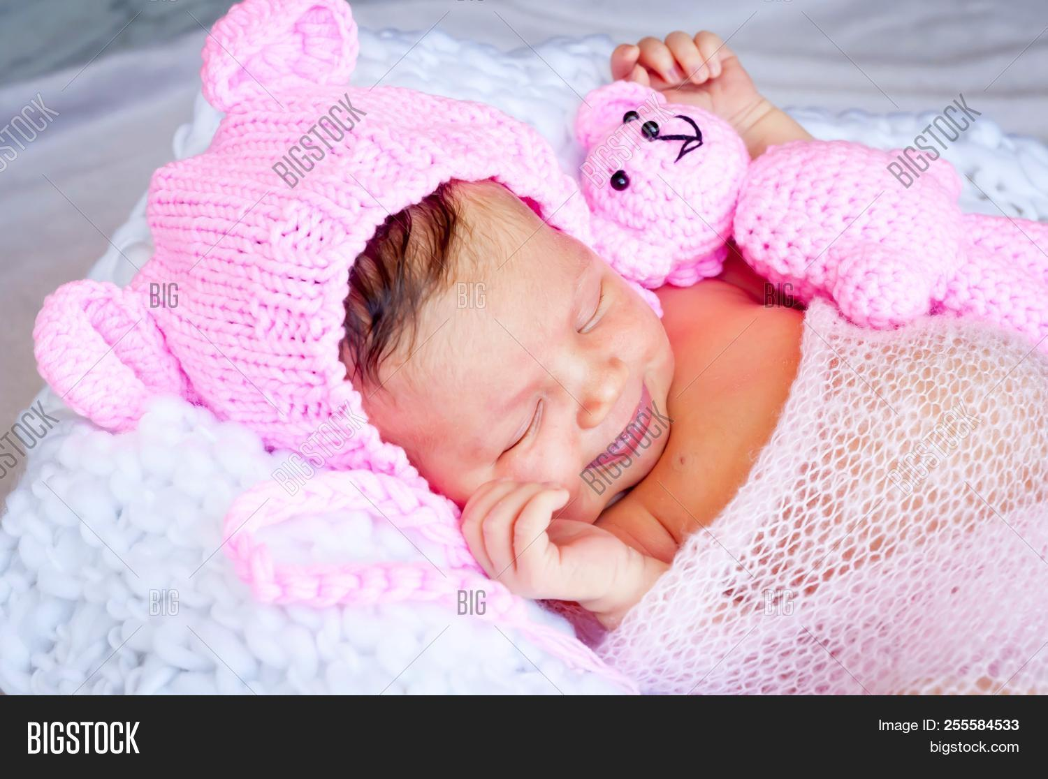▷ cute sleeping newborn caucasian baby girl in a pink hat with ears