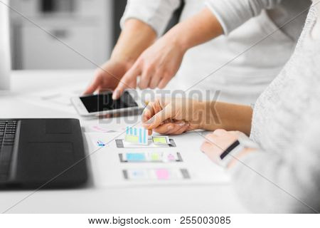 app design, technology and business concept - web designers or developers with smartphone working on user interface at office stock photo