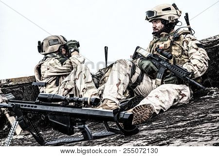 Army marksman sitting on roof observation post stock photo