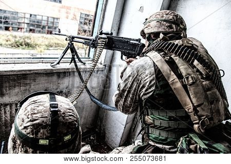 Army machine gunner attacks enemy with aimed fire stock photo