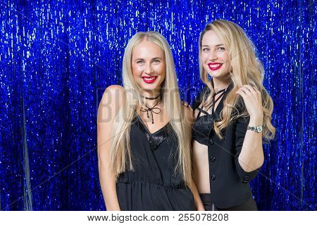 two very beautiful young blondes with make-up and a hairdo in a tight-fitting figure of black clothes are having fun and having fun at a party on a blue shiny photozone stock photo