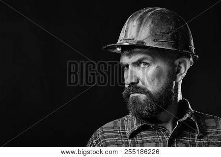 Man with distrustful face on black background, copy space. Builder or miner with thick beard. Worker with brutal image wears dirty helmet and plaid shirt. Construction and hard work concept stock photo
