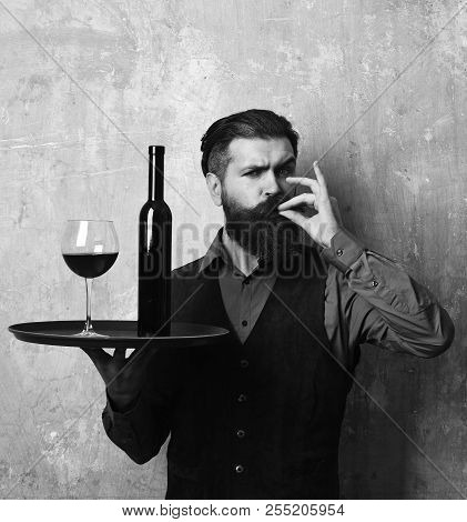 Man with beard holds wine on beige wall background. Barman with satisfied face serves wine glass showing perfection sign. Waiter with glass and bottle of red wine on tray. Service and catering concept stock photo