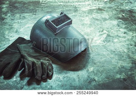 Inverted welding machine welding equipment on a wooden desk with welding mask, leather gloves, accessories for arc welding. stock photo