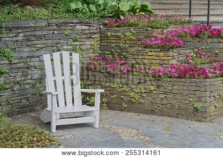 White wooden chair for relaxing at stone wall with flowers in bloom. 'Planten un Blomen' city garden in Hamburg, Germany stock photo