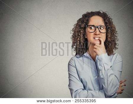 Closeup portrait nervous woman with glasses biting her fingernails craving for something, anxious isolated grey wall background with copy space. Negative human emotion, facial expression body language stock photo